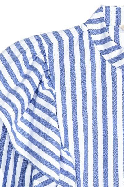 Volantbloes: Een bloes van geweven katoen met brede volants vooraan die over de schouders doorlopen tot halverwege de rug. De bloes heeft een halsboordje, een blinde knoopsluiting, licht verlaagde schoudernaden en iets wijdere mouwen met een knoopsluiting onderaan.