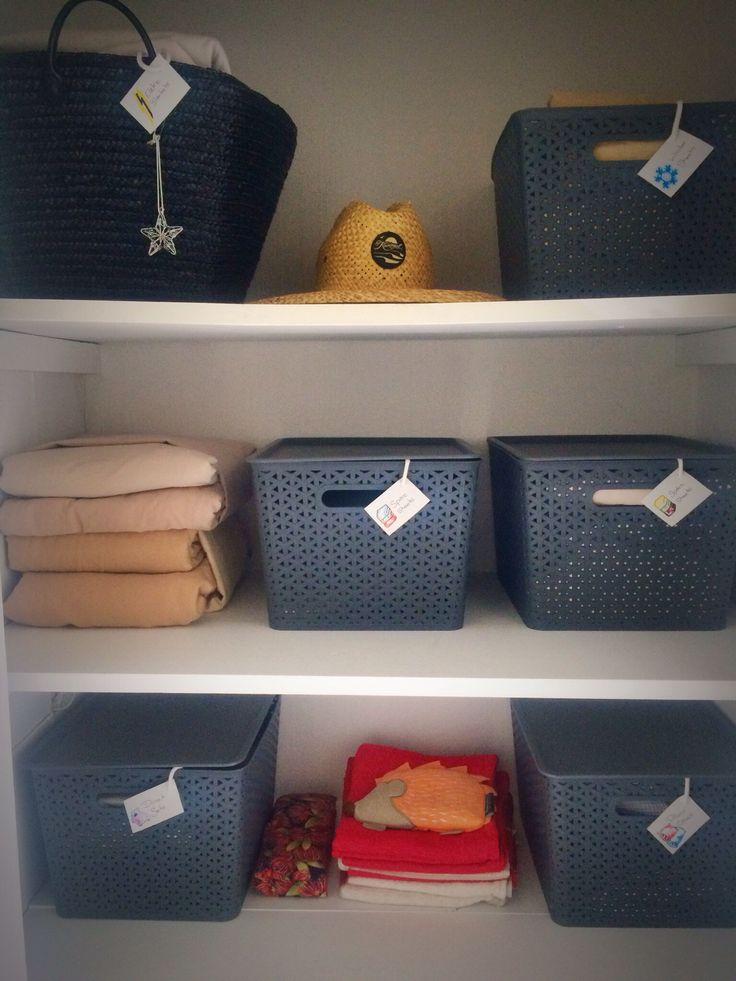Tidy storage linen cupboard organisation labels baskets folded sheets how to organise your linen cupboard.