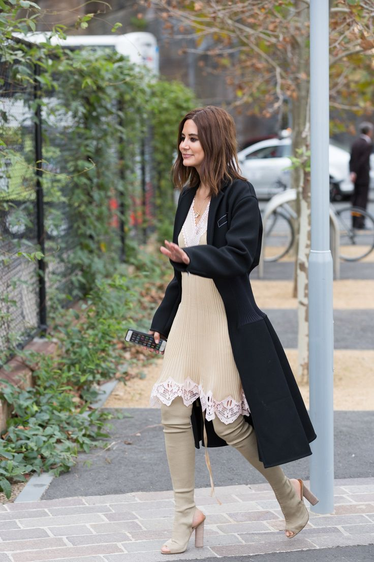 Christine Centenera wears black over coat, pleated dress with lace detailing and thigh-high boots.