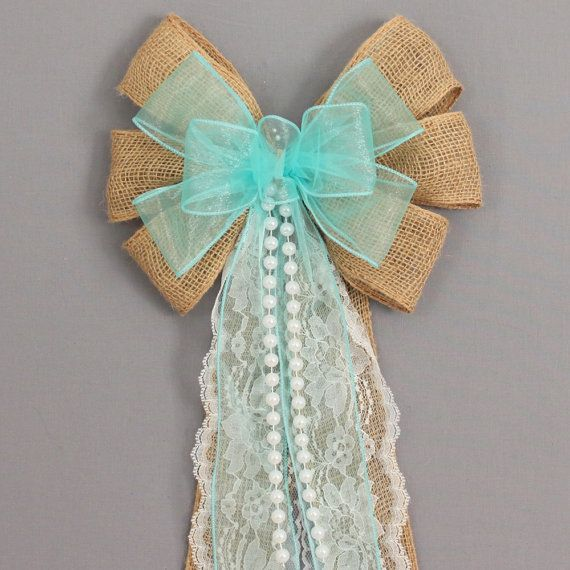 This aqua sheer burlap wedding bow is the perfect combination of burlap and lace for a rustic theme wedding. The bow features lace tails and pearls.  Bow Details: 6 loops of 2 1/2 burlap with wire edge. Note: This is real buralp so there may be minor imperfections which is the beauty of burlap. 7 loops of 2 1/2 aqua sheer with wire edge. 10 long white pearl strand (also available in ivory). Each bow also has 6 tails of the ribbon in the bow and including 2 of white lace (also available in…