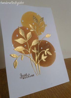 """By Julie B. CASE'd from Birgit Edblom. Die cut """"Fresh Foliage"""" (Memory Box) from 5 1/2"""" x 41/4"""" scrap cardstock. Lay the negative on front of white card base as a mask. Ink through mask with VersaMark; heat emboss with gold powder. Add dots with an embossing pen; heat emboss with silver pearl powder. Die cut or punch circle from scrap cardstock. Use the negative as a mask. Lay on card; sponge inside circle with Distress Ink. Repeat twice more with different colors of ink."""