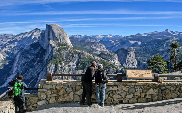 People looking out from Glacier Point towards Half Dome.