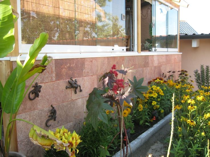Terrassenplatten aus Travertin Red als Fassaden-platten mit kleinen Eidechsen in Bronze. #wohnrausch #travertin #natursteine #terrassenplatten #mauersteine #fliesen #sichtschutz #wandverkleidung #garten
