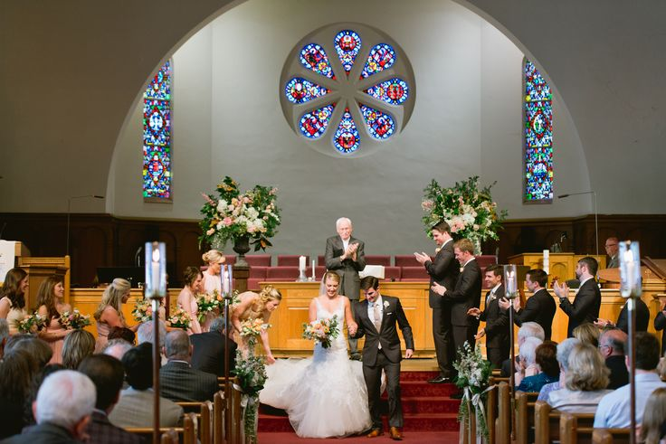 the church altar is flanked by loose urn arrangements of peach and white with abundant greenery.