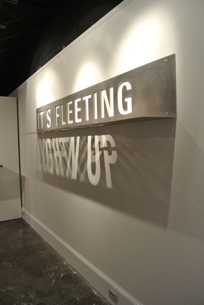 """It's Fleeting/Lighten Up is a typographic installation designed to reveal a message as it interacts with sunlight. Laser-cut into a sheet of stainless steel bent at a ninety degree angle, the piece presents two phrases, """"IT'S FLEETING,"""" and """"LIGHTEN UP."""" Laser-cut messages are cut from both planes—one with the message """"IT'S FLEETING"""" and the other with """"LIGHTEN UP"""". Installed at eye level and flush against the wall, """"IT'S FLEETING"""" is always be visible and """"LIGHTEN UP"""" is revealed as shadow."""