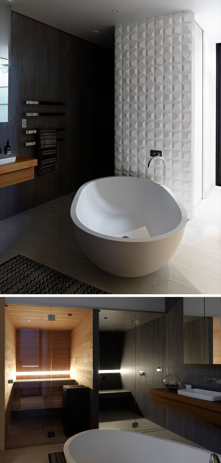 This modern bathroom features decorative 3-dimensional tile wall, a standalone bathtub, a shower with built-in seat and a sauna.