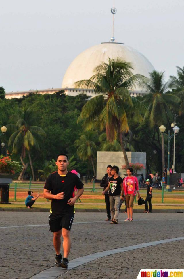 Terlihat seorang pengunjung sedang berolahraga jogging berkeliling di pelataran Monas, Jakarta.