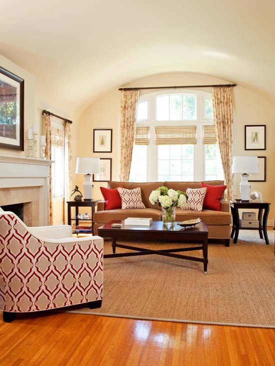 burgundy + beige = relaxing color scheme. vibrantly hued funishings atop a seagrass rug in living room. chair fabric = white wool on front, colorful pattern on back. same pattern appears in pillows on sofa. softly patterned curtains take fabric to ceiling heights, drawing eye to wide barrel vault