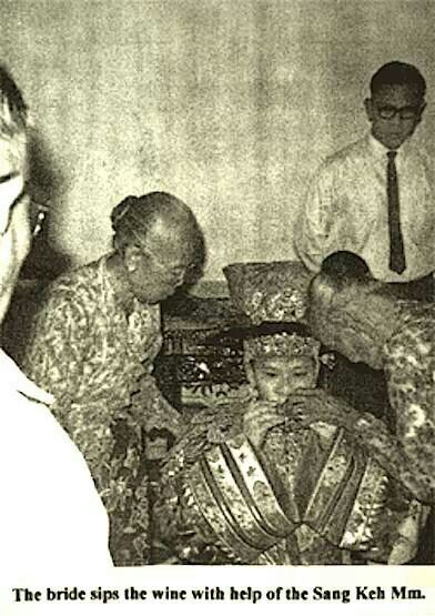 """A Peranakan Wedding...The Bride is being assisted by the """"Sangkek Um""""( Matron Dresser) on the right side of the Bride..+ is assisted by another lady know as the """"Bukak- koon""""who helps with the Bridal gown."""