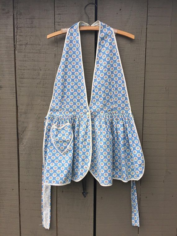 Darling hand made 50s cotton full farm apron with heart pocket and unusual design. Very good condition. All of our items are used/vintage pieces that have wear consistent with age. We always do our best to show and/or describe all of the vintage characteristics. Please feel free to convo us if you have specific questions. We ship internationally .