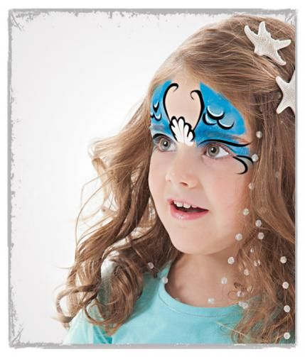 """Girls: mermaid tutorial Sponge blue face paint over the eyes and up onto the forehead. With a brush, paint a white shell in the center of the forehead and scales (or """"U"""" shapes) on the blue forehead. Outline in black paint. Draw a black line on the eyelids and two black lines at the corner of each eye."""