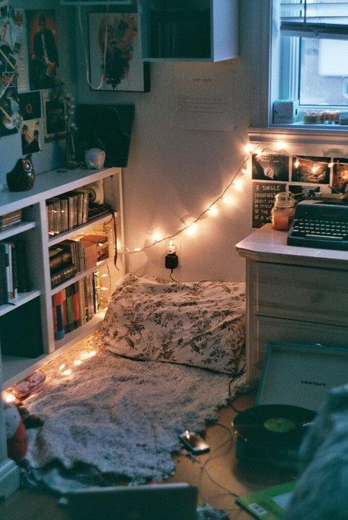 Typewriter, photos, bed on floor, books, records, chest o drawers