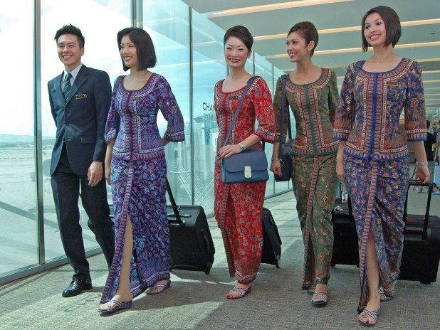 Crew uniform colours of Singapore Airlines. L-R. Leading Steward (LS, green tie), In Flight Supervisor female (IFSS, purple Sarong Kebaya), Chief Stewardess (CSS, Red), Leading Stewardess (LSS, Green), Flight Stewardess (FSS, Blue). The picture also represents the three major ethnic groups of Singapore. Chinese, Indians, Malays. Photo courtesy Changi airport.