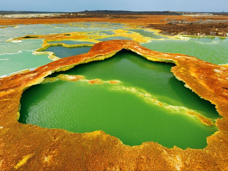 Hot Springs, East Africa - Sulfur and algae turn hot springs into pools of living color. The water is condensation from hot gases rising from magma chambers. As the water evaporates, salts and minerals form a vivid crust