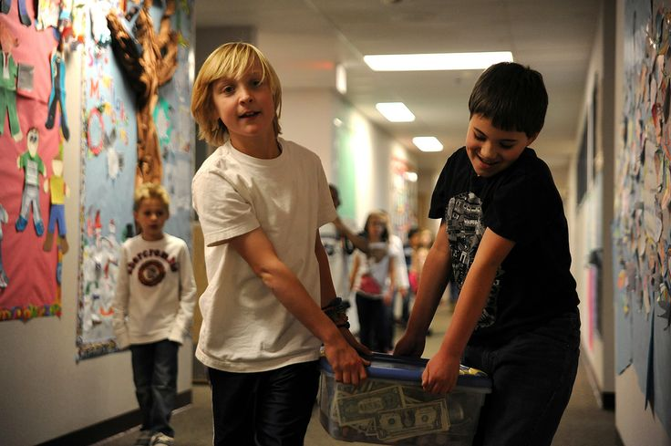"Fifth graders Logan Duncan, 10, and Logan Nestelroad, 10, carry the results of a ""quarter war,"" a weeklong schoolwide event that raised funds for the Wounded Warrior Project, Dec. 17 at Remington Elementary School in Falcon School District 49. Duncan and Nestelroad spent time after school the past week to count each classroom's donations and make deposits. With the results tallied, they traveled to second grade teacher Trisha Butler's classroom to tell her students they raised the most…"