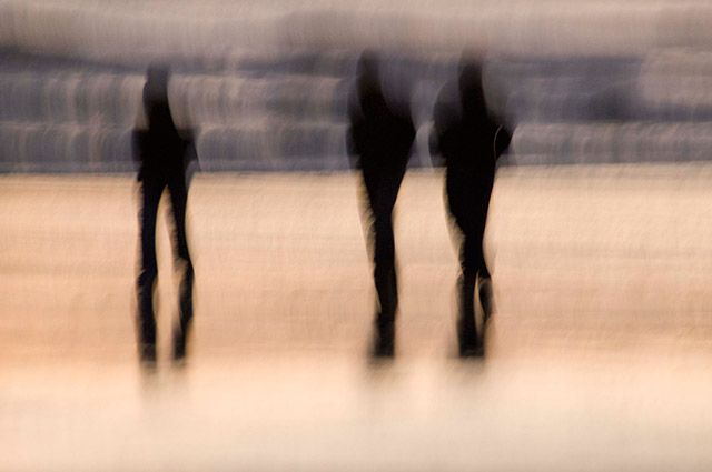 Impressionistic image of 3 silhouetted people by Eva Polak.