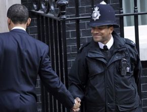 """This is the most powerful photo in the series. Remember they are not supposed to shake hands, but the two brothers couldnt resist the historic moment. The police guard never imagined in his wildest dream that he would usher a black American president into the British corridors of power."""