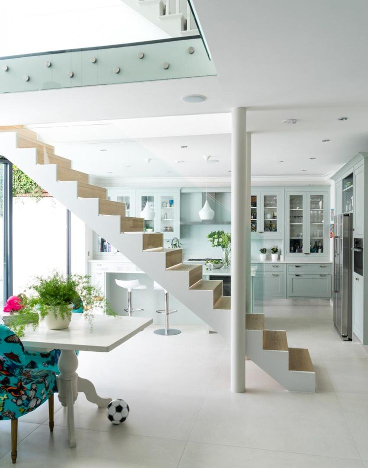 Zoning off the kitchen diner is an impressive suspended staircase; slender gaps in the wood risers let slivers of sunlight shine through which adds to the feeling of airy weightlessness.