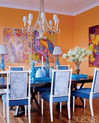 The blue hue is the dominant color in this dining room. The yellow-orange walls and hints of red-orange in the paintings combine to create a split-complementary color scheme.