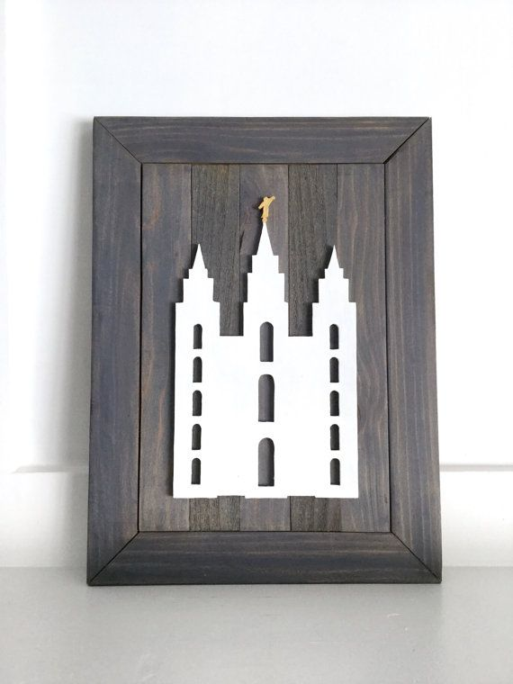 Custom made, all wood LDS temple wall art. This custom made piece features a hand-cut silhouette of an LDS temple on a hand-made pallet frame. We are able to do any LDS temple of your choice (temples shown are the Salt Lake City, Utah and Idaho Falls, Idaho temple). It comes ready to hang with a sawtooth hanger already attached to the frame. Great for wedding, 5th anniversary, and housewarming gifts!  We have multiple stain, color, and frame options to choose from to make this a truly custom…