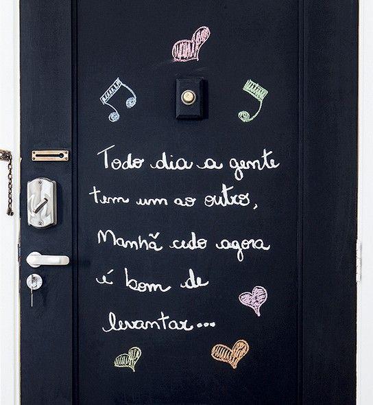 A parte interna da porta de entrada foi pintada com tinta lousa preta e ganhou o trecho de uma canção de Mallu Magalhães, que aumenta o clima de romantismo no apartamento do casal Vanessa Gonçalves e Dante Calligaris