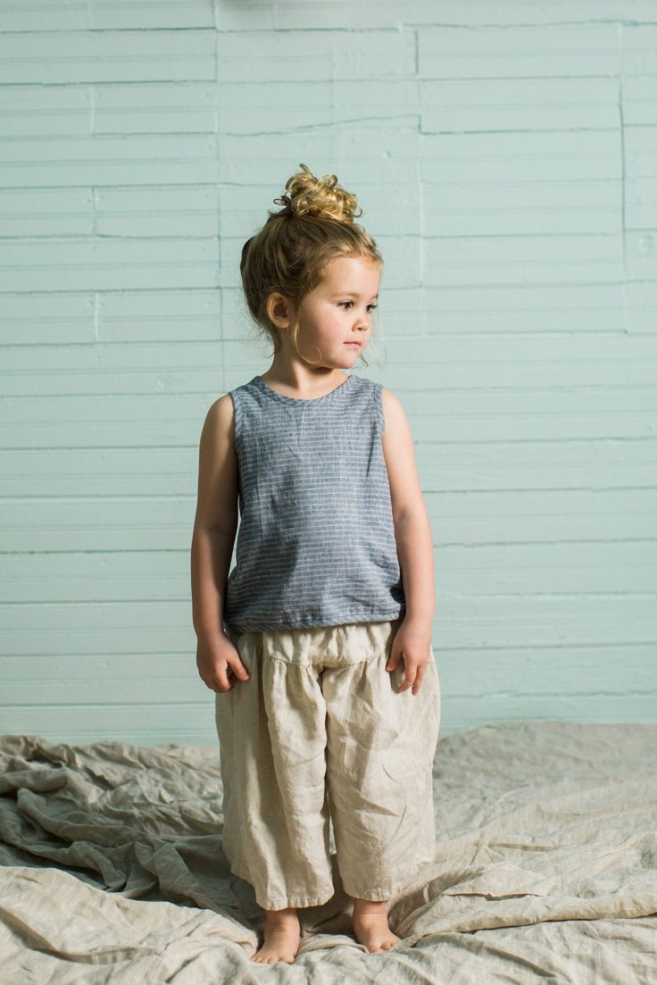 Our favorite summer piece for boys and girls. Lightweight, slips on over the head, with no closures to fuss with. Straps criss-cross in the back. In a blue and white woven stripe. The fibers of this f