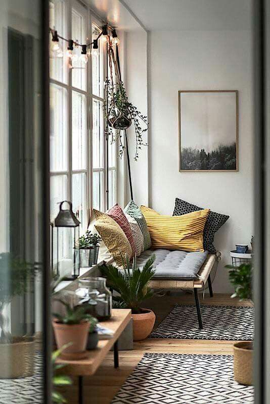 Love everything in this photo | Big window, picture, lights, plants, cushions and rugs !