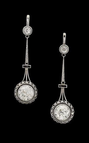 A pair of diamond pendant earrings, circa 1920 Each old brilliant-cut diamond, within a pierced collet setting, suspended from a smaller old brilliant-cut diamond by an engraved tapered baton and a synthetic sapphire bar, principle diamonds approx. 3.00 carats each. (hva)