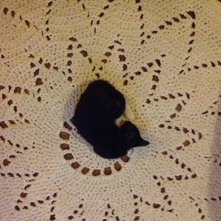 Virkattu matto, jonka halkaisija on noin 140cm. Musta mytty on 9vko Bindi Kisunen.