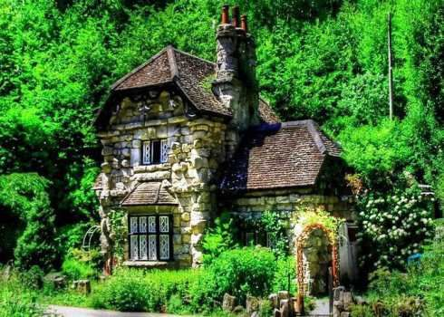Appearing to have popped from the pages of a Brothers Grimm fairy tale, an enchanting stone cottage nestles in a woodland setting in The Neth- erlands (below).  The romantic two story pile features projecting stone- work at the corners, flanked by one story wings.    A bay window with decorative casements adorns the facade.   Overhead,  a soaring stone chimney punctuates the multilevel clipped gable roof.