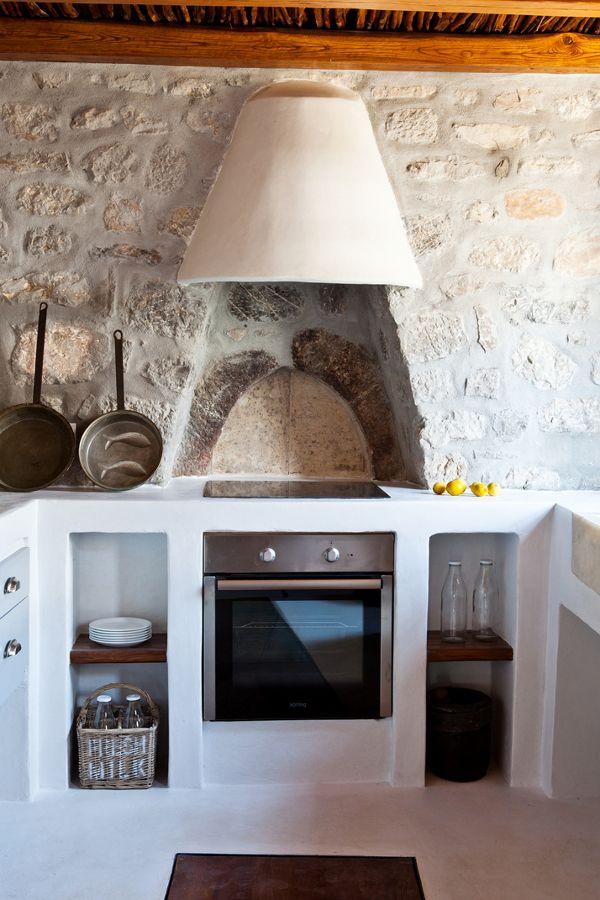 Griega en blanco, con estantes de madera y paredes en piedra