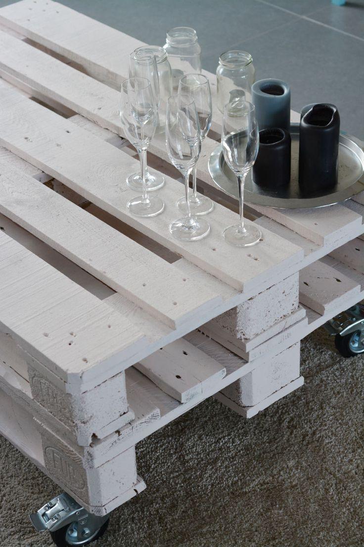 DIY: oud pallet wordt salontafel: 2 paletten in goede staat, witte verf, schuurpapier, vier wieltjes waarvan minstens 2 met rem. schuren, 2 lagen geven, eenmaal droog remmen bevestigen. plaats 2 paletten boven mekaar, en lijm vast.