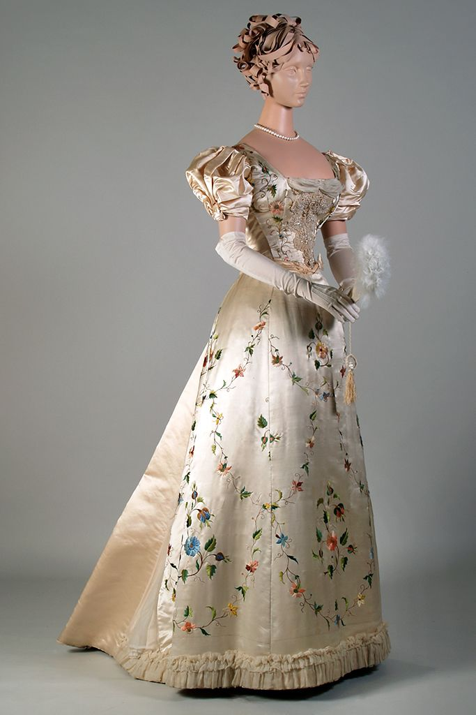"""Ivory satin evening dress with multicolored Chinese floral embroidery, pearl and braid trim, and inset chiffon, label: """"Mme Marie Reeves, Robes et Manteaux, 52 E. 21 St., N.Y."""" ca. 1895, KSUM 1983.1.209."""