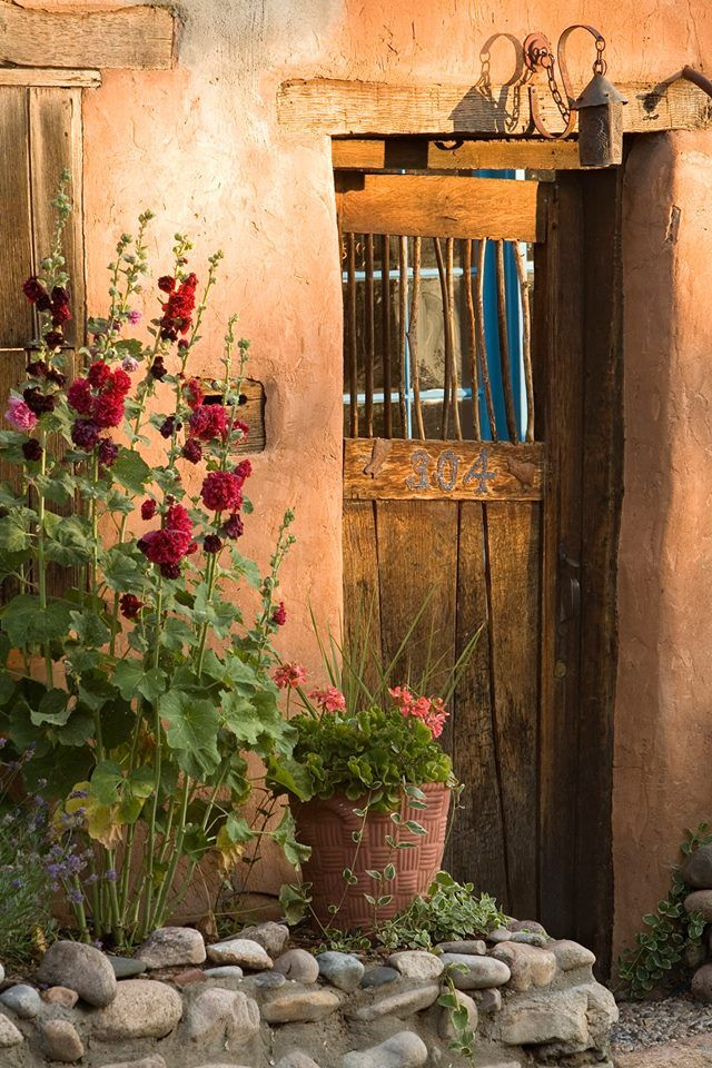Santa Fe style -hollyhocks and old doors and adobes made of terracotta clay