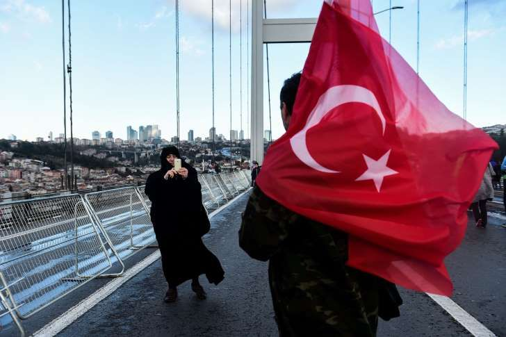 A woman takes a picture of a man holding Turkish national flags on the July 15 Martyrs' Bridge, known as the Bosphorus Bridge, during the 38th annual Istanbul Marathon on November 13, 2016.