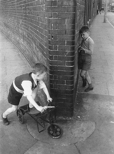 Children of the Streets, August 1954  One young boy ambushing another around a street corner, each with his toy gun at the ready   Thurston Hopkins