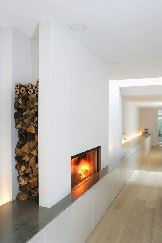 Double-faced fireplace 21/85 by Stûv (www.stuv.com) with retractable glass doors to create the effect of an open fire if desired. Creative design idea for log storage.
