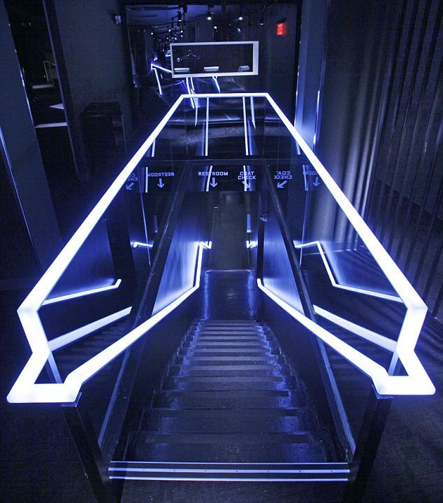 So here we have a futuristic looking escalator. It has the neon lights and the glass, although the actual stair pieces look older because they're a bit dirty and have a rough texture.