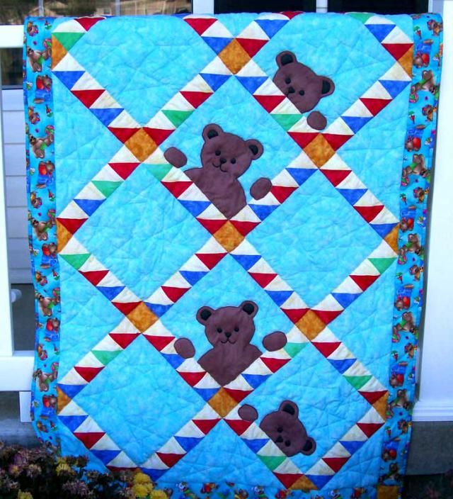 Bears, peeking across rows of half square triangle units in this colorful baby quilt. By Sandi Gieson