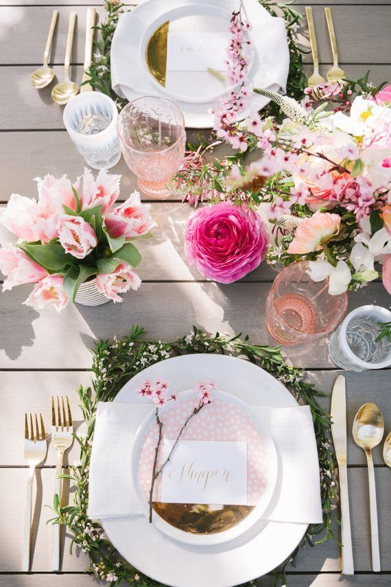 Beautiful spring decoration for the table. Pale pink flower bouquet with golden cutlery & a plate bedded on greens.