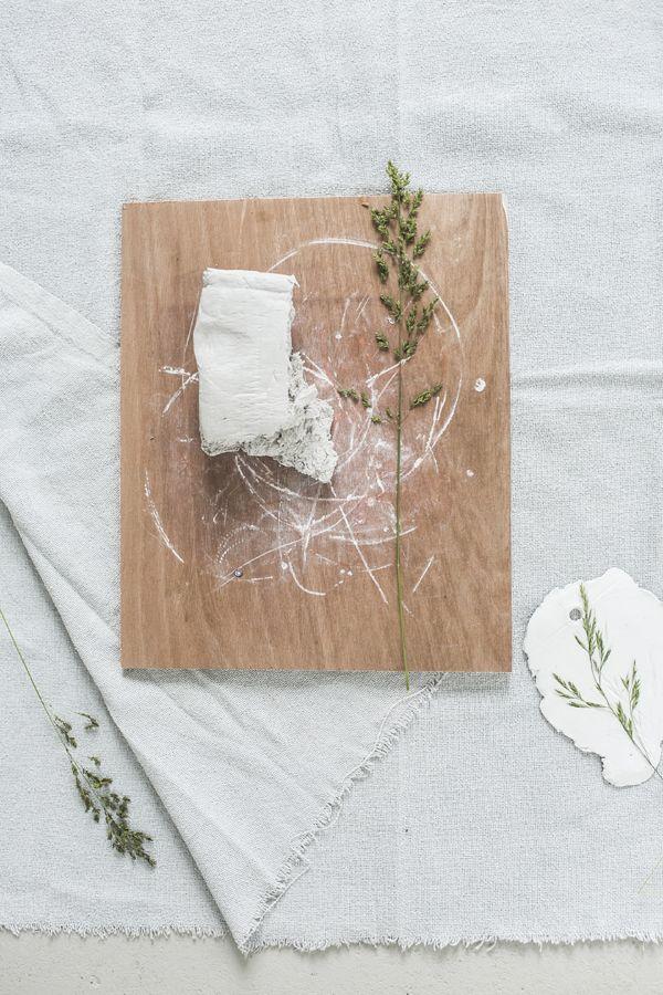 Stap 1   Vorm en knoop geometrische vormen van de grassprieten en leg ze te drogen in een bloemenpers of in vloeipapier tussen een stapel boeken. Stap 2   Trek een grof stuk uit de homp witte klei en rol deze ongeveer tot 1 cm dikte. Stap 3   Leg 1 van de gedroogde geo grassen op het plak klei (bepaal zelf een mooie compositie, hij hoeft natuurlijk niet helemaal passend op de klei;-) en rol het gras een stukje mee, zodat hij vast komt te zitten in de klei. Stap 4   Maak met de potlood/pen…