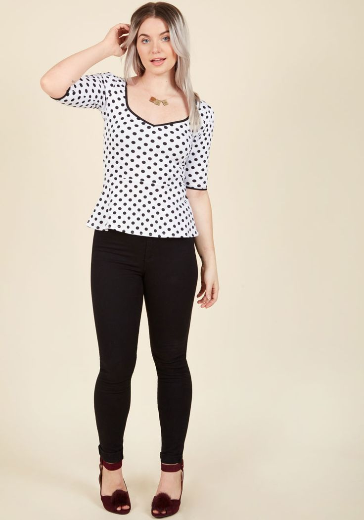 You're one ebullient citizen when you reside in this polka-dotted peplum top! Sprinkled with black spots atop a white backdrop, this knit shirt has smile-inspiring amounts of flounce in its pleated shoulders and a flattering angled silhouette. The scooped, sweetheart-esque neckline boasts dark trim, while the flexible, formfitting fabric leaves you feeling animated, especially when teamed up with a cherry-hued tulip skirt and noir peep toes. You've got metropolitan moxie w...