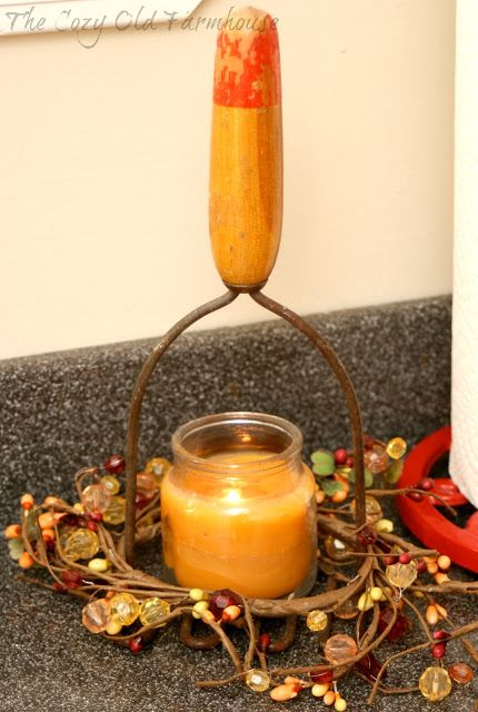 fall candle cradled in old potato masher with berry wreath
