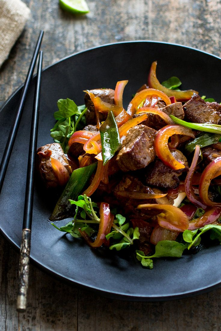 "NYT Cooking: This savory-sweet stir-fry, known as <i>bo luc lac</i> or ""dice"" in Vietnamese, gets its English name from the constant shaking of the pan performed by the cook while browning the meat. It can be tough work to move the hot wok constantly, and the intense heat can burn the ingredients in a wink. This recipe, adapted from the one served at Slanted Door, Charles Phan's%..."