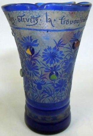 """mile GALLE (1846-1904), vase parlant """"Les bleuets la trouvaient belle, V. Hugo"""", vase évasé trilobé en verre blanc à décor de bleuets en verre bleu camé dégagé à l'acide. Il est appliqué de 10 cabochons à inclusion de feuille d'or et vert. Le fond est décoré en camé d'un bleuet, signature manuscrite à l'or """"Emile Gallé fecit"""", croix de Lorraine avec initiales EG ainsi que daté 1891. Hauteur : 20,5 cm"""