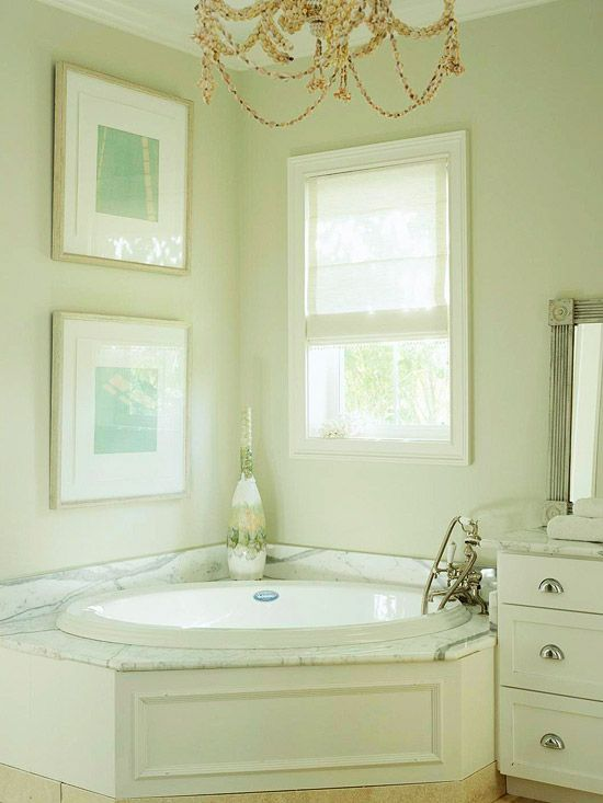 Nestled in a platform of marble, this soaking tub is the definition of elegance. A recessed panel along the front of the surround further carries the graceful design, as does the vintage-inspired faucet./