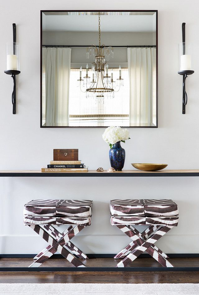 Glam entryway with a simple mirrors, matching sconces, a wooden table styled with books and flowers and animal print stools