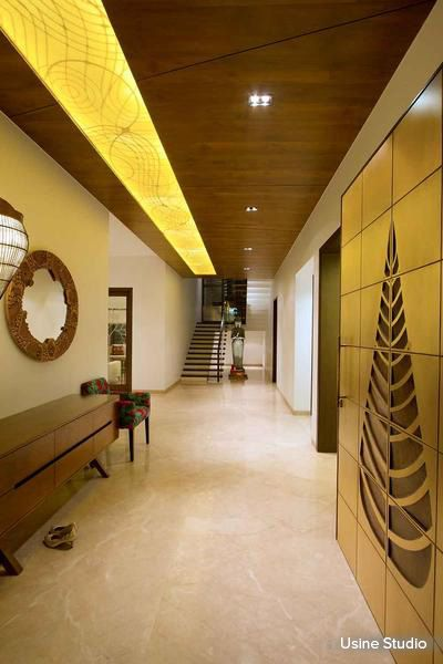 Stunning golden wall art, concealed dim yellow lighting and a dark wooden ceiling are all complimented with a light pastel marble flooring; giving each element a voice of its own #homedecor #designs #wallart #foyer Design Courtesy - Usine Studio, Vadodara