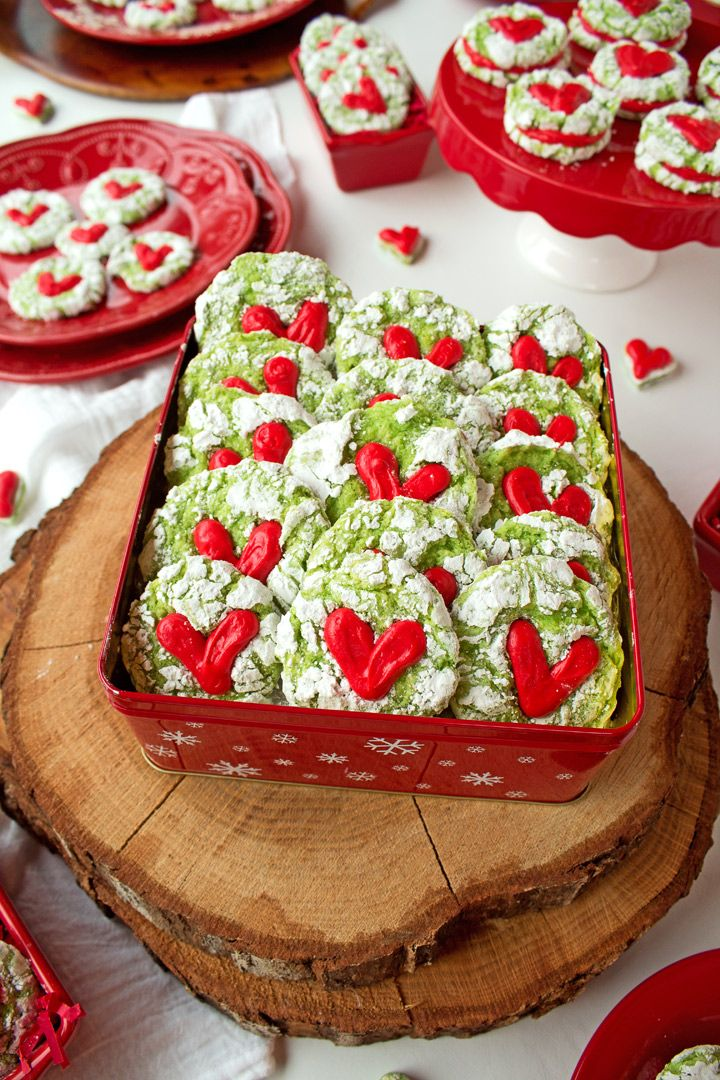 Simple Grinch Cookies made from a Lemon Cake Mix and rolled in powdered sugar and topped with a cute heart made with cream cheese frosting.
