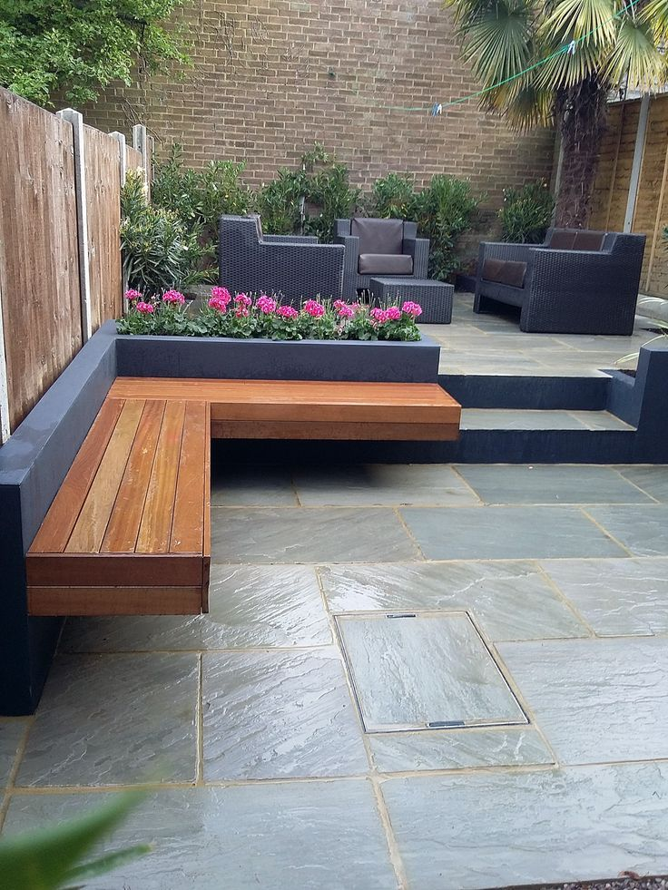 hardwood bench seat grey render block walls raised beds grey sandstone paving patio.